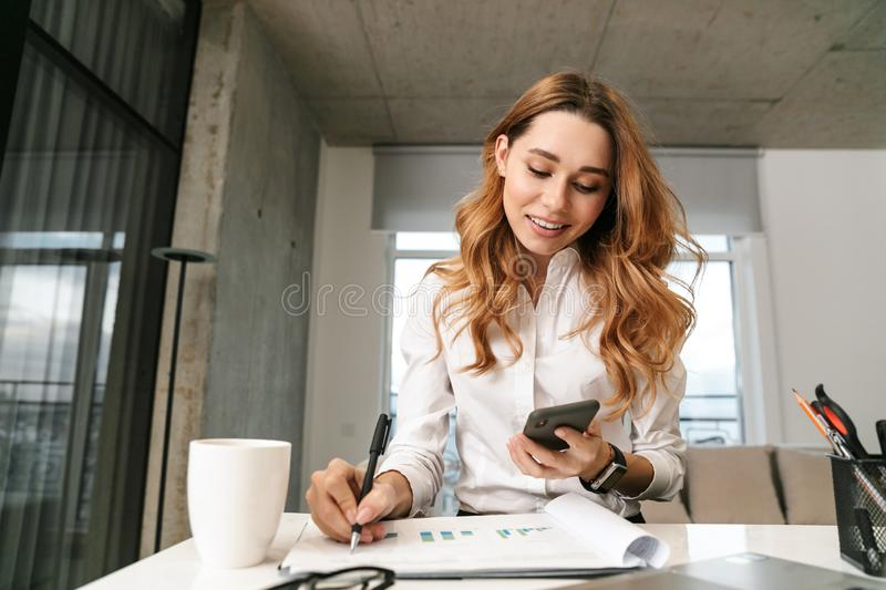 Woman dressed in formal clothes shirt indoors using mobile phone writing notes stock images