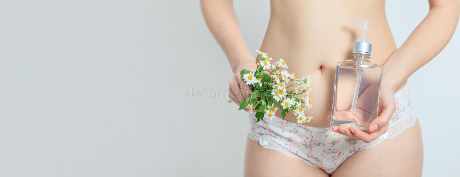 A woman dressed in panties holds chamomile flowers and a bottle with gel for care in her hands, close-up. women`s health stock photo