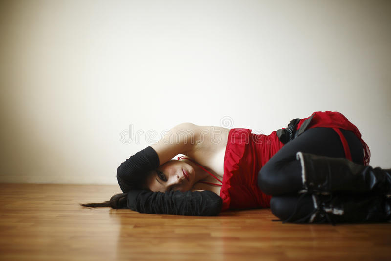 Woman dressed in red and black. Attractive young woman wearing red and black on a wood floor stock photography