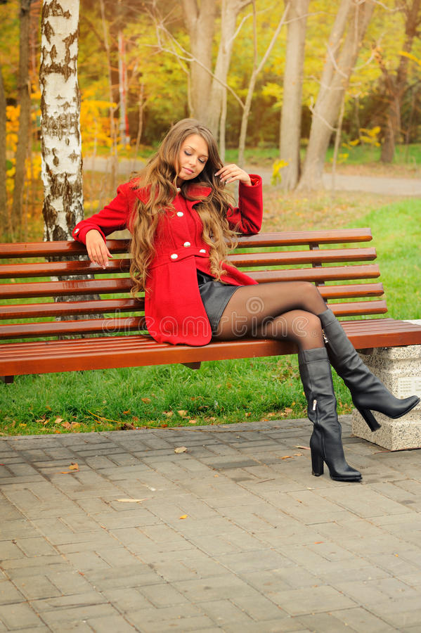 Woman dressed in red coat sitting in autumn park. royalty free stock photography