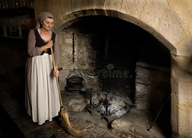 Woman cleaning at medieval fireplace royalty free stock images