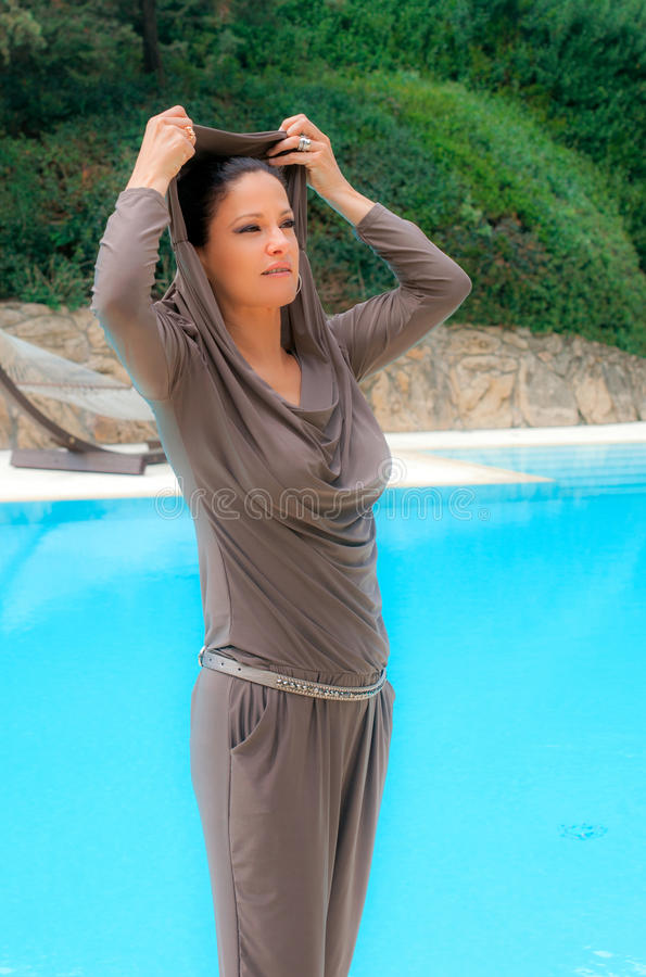 Woman dressed in silver-gray relaxes by the pool royalty free stock image