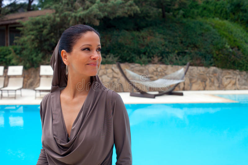 Woman dressed in silver-gray relaxes by the pool stock images
