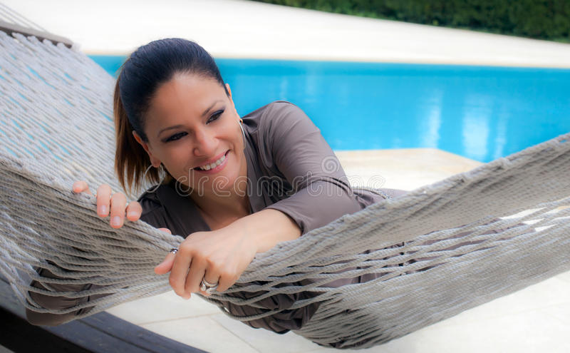 Woman dressed in silver-gray relaxing on a hammock stock photo
