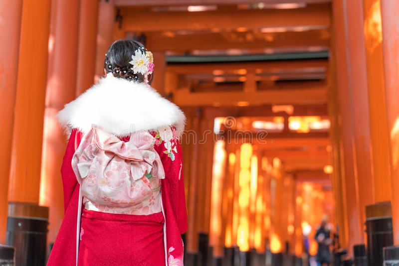 Woman dressed in traditional japanese costume walking under Red royalty free stock images