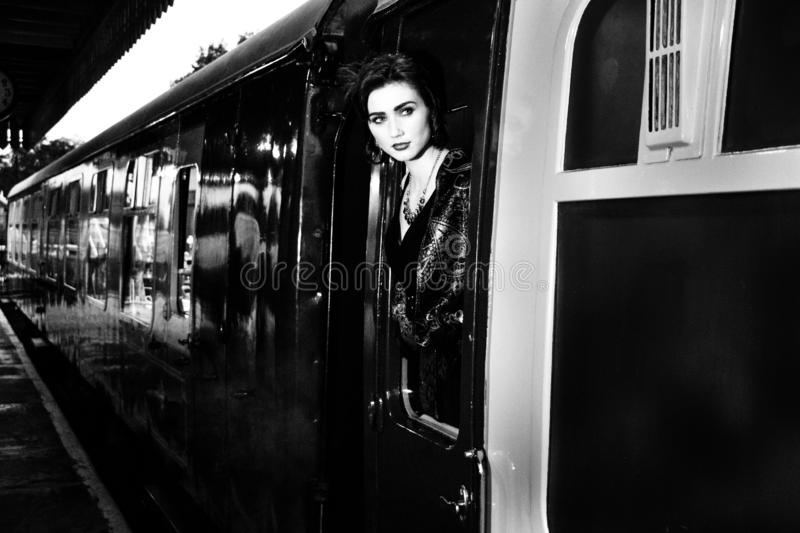 Woman dressed in vintage evening dress leaning out of train window and blowing a kiss. Attractive woman, female wearing vintage evening dress leaning out of royalty free stock photo