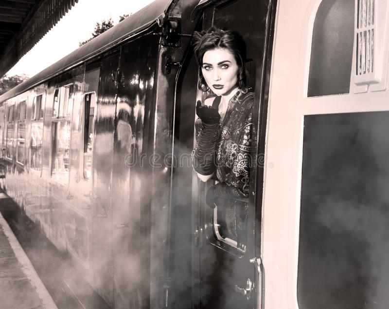 Woman dressed in vintage evening dress leaning out of train window and blowing a kiss. Attractive woman, female wearing vintage evening dress leaning out of stock images