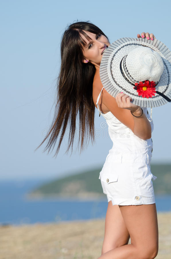 Woman dressed with white coveralls rompers joying the sunny day stock photos