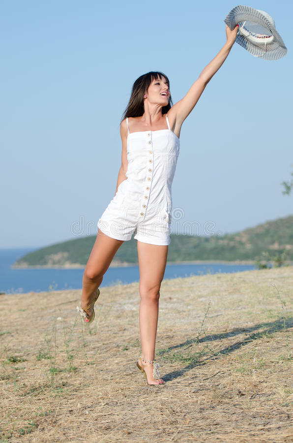 Woman dressed with white coveralls rompers joying the sunny day stock photography