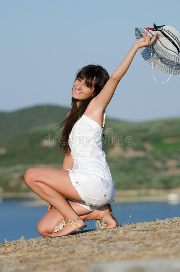 Woman dressed with white coveralls rompers joying the sunny day. Woman dressed with white coveralls rompers and packable floppy straw sun hat, joying the sunny royalty free stock image