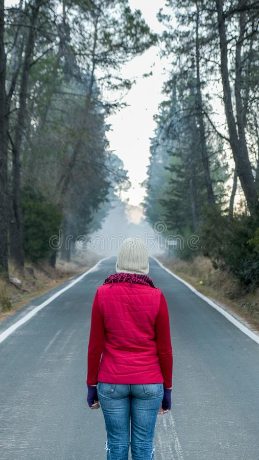Woman dressed in winter with her back in the middle of a lonely road that crosses a forest. royalty free stock photo