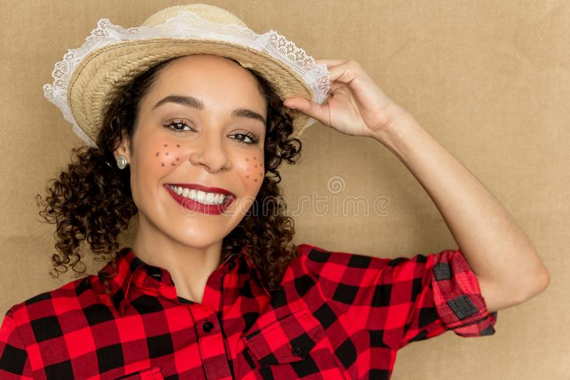 Woman dressing checked pattern clothes on rustic background. Brazilian girl wearing red plaid shirt holding the hat stock photography