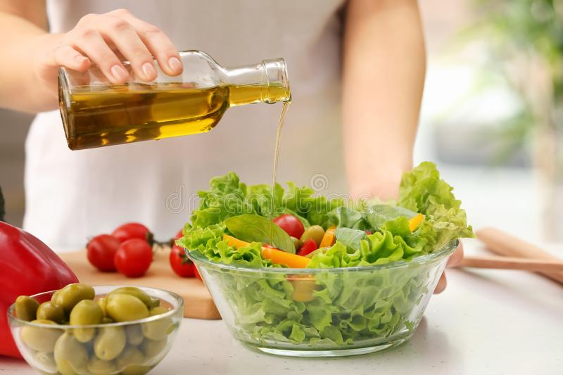 Woman dressing fresh vegetable salad with olive oil in kitchen royalty free stock photography