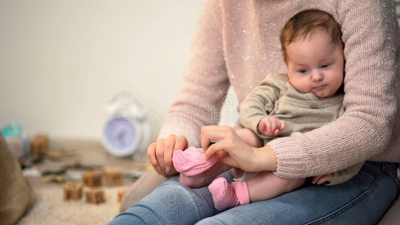 Woman dressing little cute infant girl in pink socks, natural clothing materials stock images