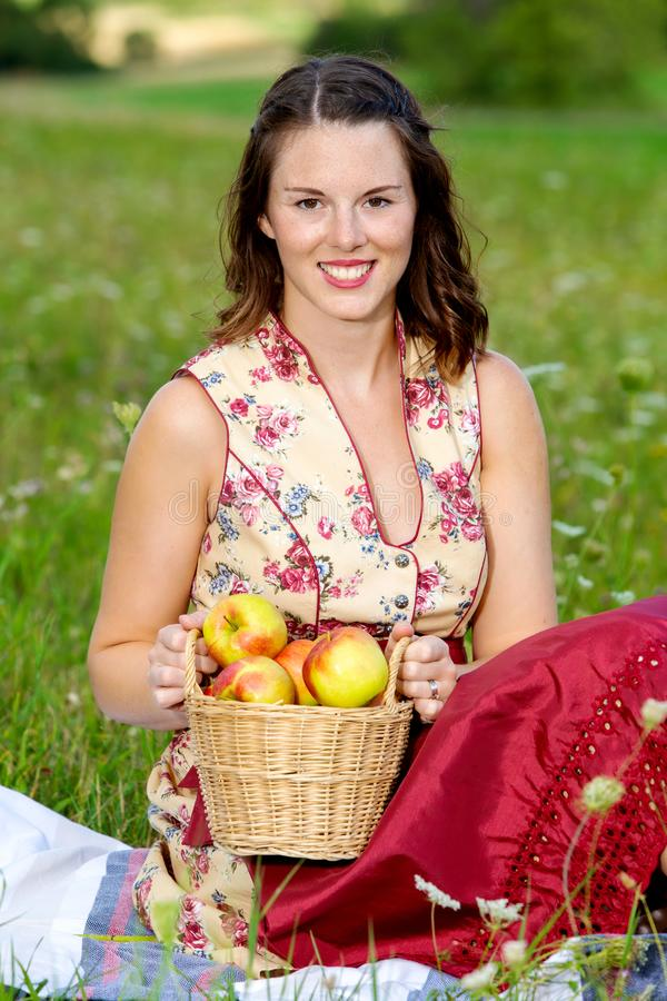 Woman in drindl sitting in a meadow and holding a basket with apples. Young woman in drindl sitting in a meadow and holding a basket with apples royalty free stock photography