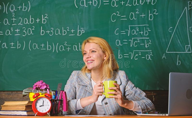Woman drink coffee in classroom. teacher with alarm clock at blackboard. Time. Back to school. Teachers day. Study and royalty free stock photo