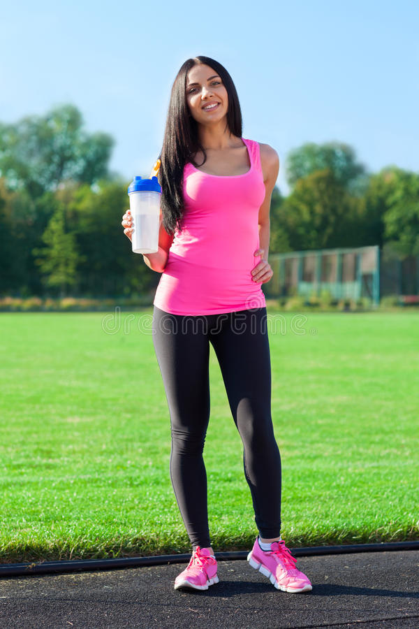 Woman drink water bottle sport on stadium. Summer outdoors training, girl morning fitness exercises stock photography