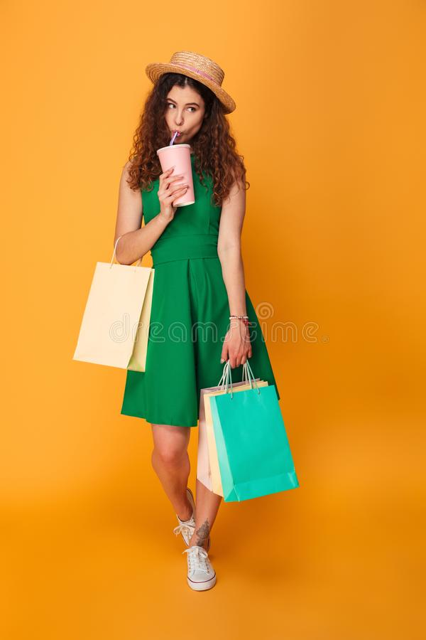 Woman drinking aerated water holding shopping bags. Image of young woman standing isolated over yellow background. Looking aside drinking aerated water holding stock image