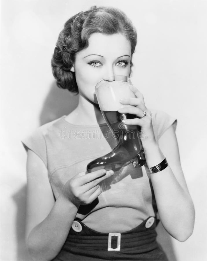 Woman drinking beer out of a boot shaped glass. (All persons depicted are no longer living and no estate exists. Supplier grants that there will be no model stock image
