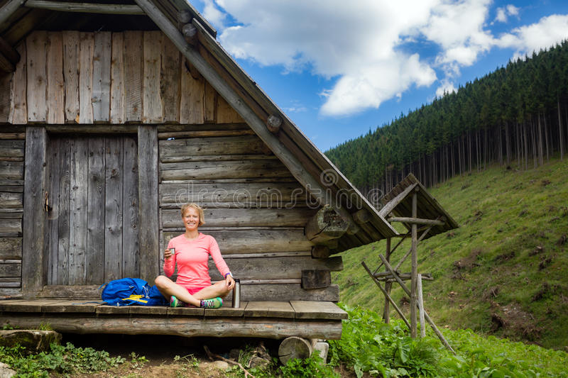 Woman drinking and camping in inspiring mountain landscape. Young woman hiker camping, drink coffee or tea in beautiful Tatra mountains on hiking trip stock photography