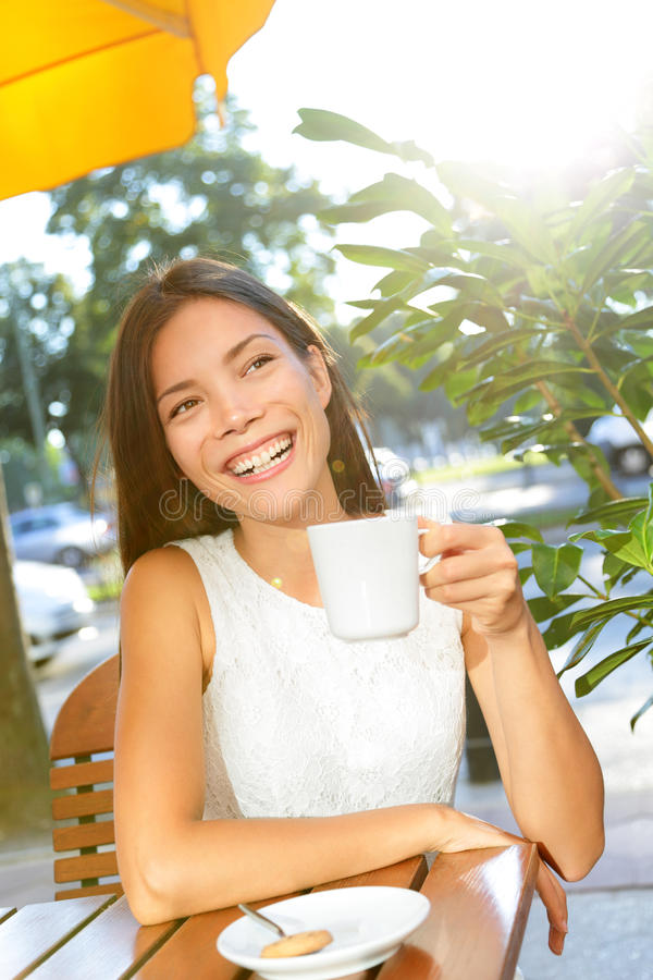 Woman drinking coffee at cafe stock photo
