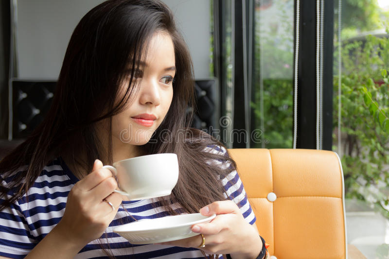 Woman drinking coffee at cafe stock image