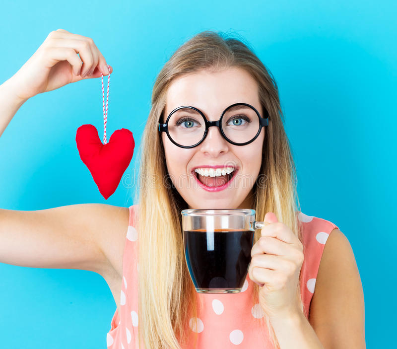 Woman drinking coffee with heart cushion royalty free stock photography