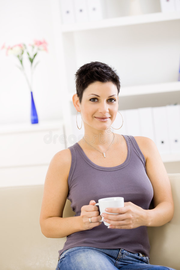 Woman drinking coffee at home. Young woman wearing jeans and tank top, sitting on couch at home, drinking coffee, smiling stock image