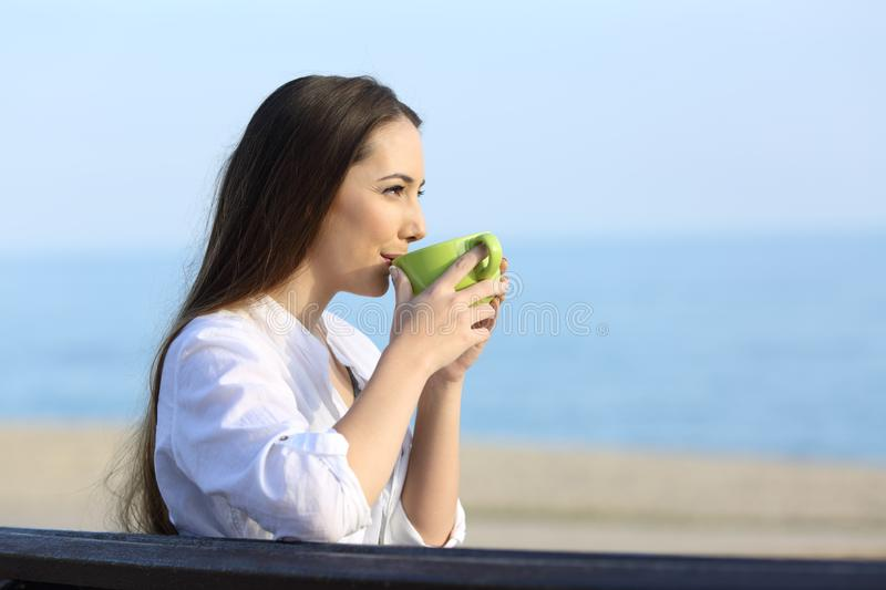 Woman drinking coffee and looking away on the beach stock image