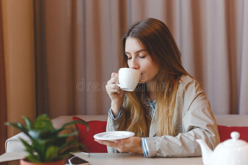 Woman drinking coffee in the morning at restaurant soft focus. Closeup portrait of the pretty girl with cup tea royalty free stock image