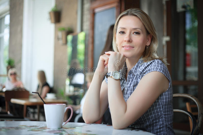 Woman drinking coffee in the morning at restaurant. stock photo