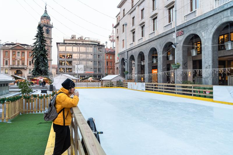 Woman is drinking coffee near the ice rink on the Monte Grappa square in the center of Varese at Christmas time, Italy stock image