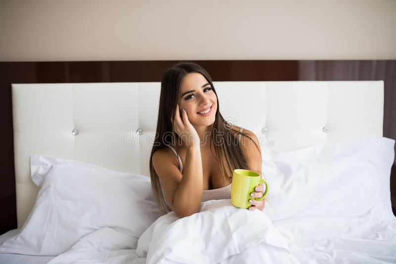woman drinking coffee while sitting in bed stock photography