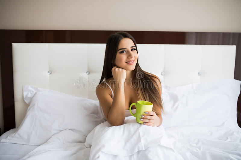 woman drinking coffee while sitting in bed stock images