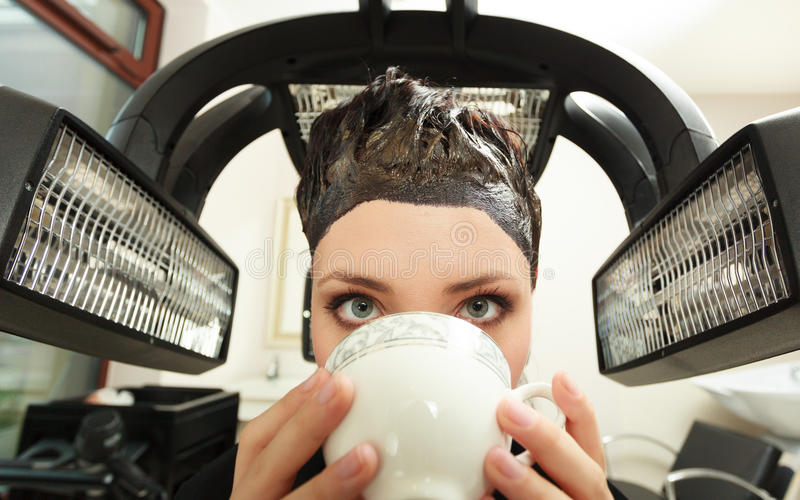 Woman drinking coffee tea in hair beauty salon. By hairdresser. Young woman drinking coffee tea in hairdressing beauty salon. Girl dying colouring hair by royalty free stock image