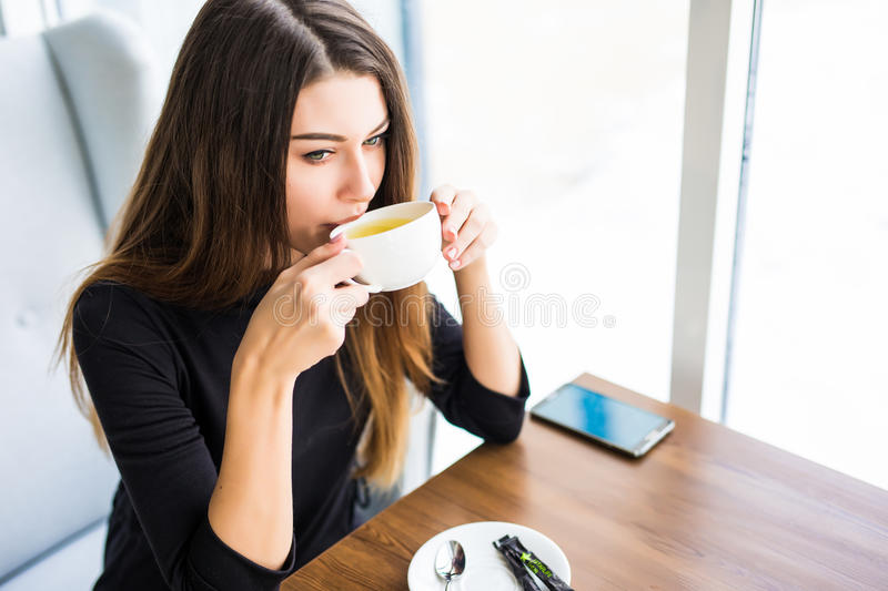Woman drinking coffee or tea in the morning at restaurant. Closeup portrait of the pretty girl with cup of tea stock images