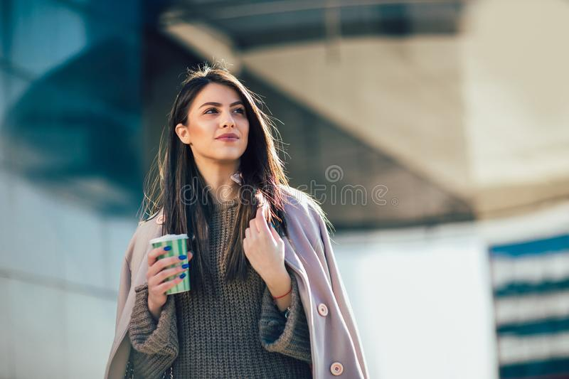 Woman drinking coffee to go in a city street stock image