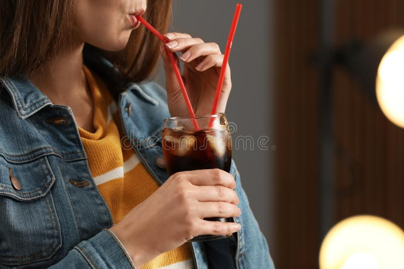 Woman drinking cola from glass against blurred background royalty free stock image