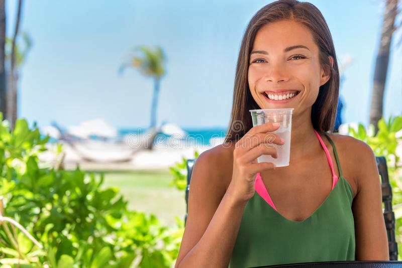 Woman drinking cold water drink glass at outdoor cafe hotel resort on beach holidays. Healthy girl staying hydrated during warm stock photos