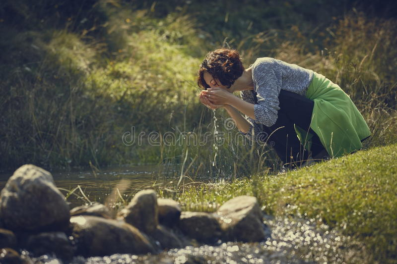 Woman drinking creek fresh water stock images