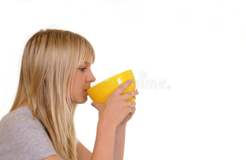 Download Woman drinking from a cup stock photo. Image of yellow - 15959514