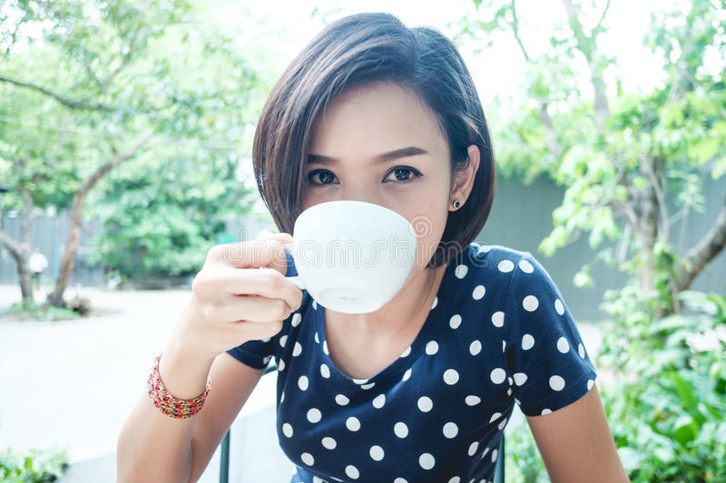 Woman is drinking a cup of coffee royalty free stock photo