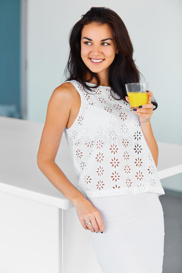 Woman drinking fresh orange juice in the kitchen. Happiness, wel royalty free stock photography
