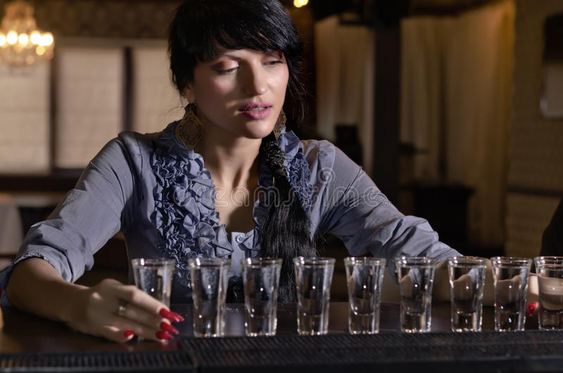 Woman drinking heavily at a bar royalty free stock photography
