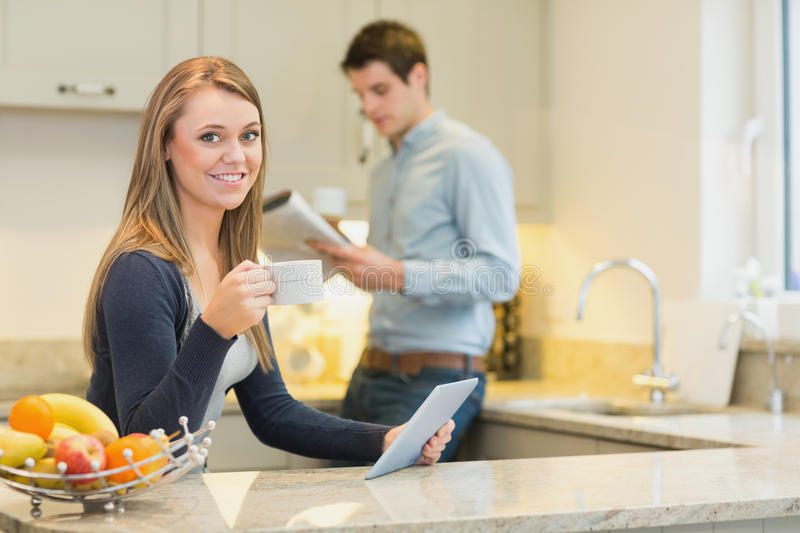 Download Woman Drinking Hot Beverage Using Tablet Pc In Kitchen Stock Photos - Image: 31098303