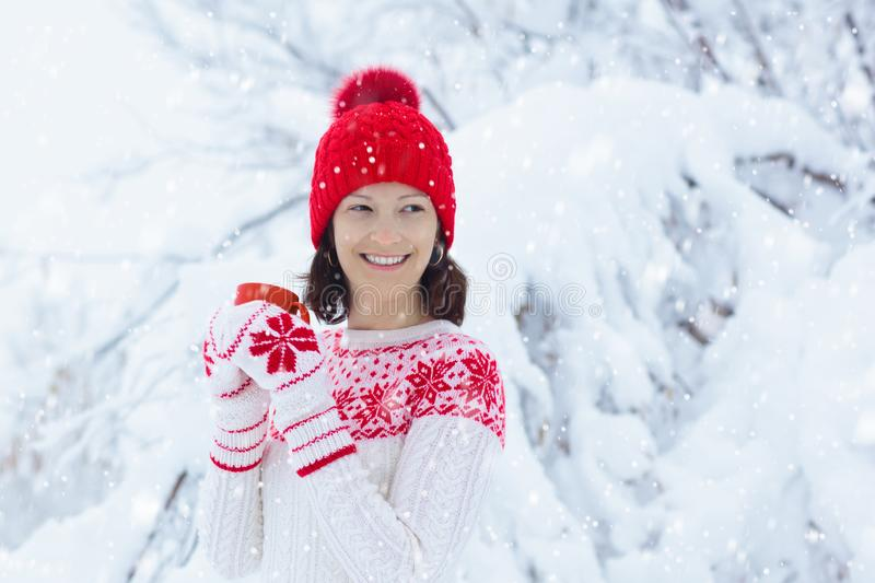 Woman drinking hot chocolate in Christmas morning in snowy garden. Girl in knitted Nordic sweater, hat and mittens holding cup stock photos