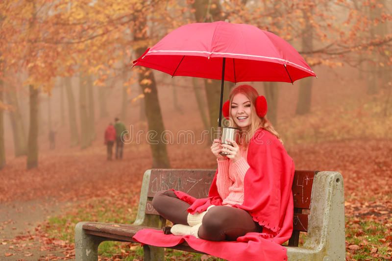 Woman drinking hot coffee relaxing in autumn park. Woman with umbrella sitting on bench drinking hot cofee or tea relaxing in fall park. Young blonde girl stock photos