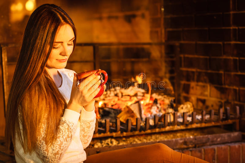 Woman drinking hot coffee relaxing at fireplace. Woman drinking cup of coffee relaxing at fireplace. Young girl with hot beverage heating warming up. Winter at royalty free stock photos
