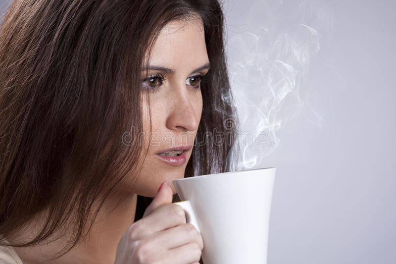 Woman drinking a hot drink. Beautiful woman portrait holding a mug with some hot drink stock photography