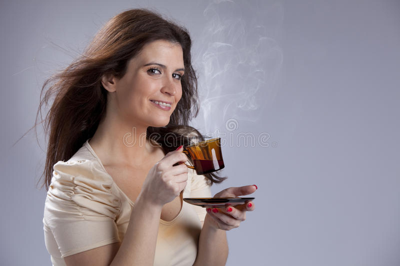 Woman drinking a hot drink. Beautiful woman portrait holding a mug with some hot drink royalty free stock photography